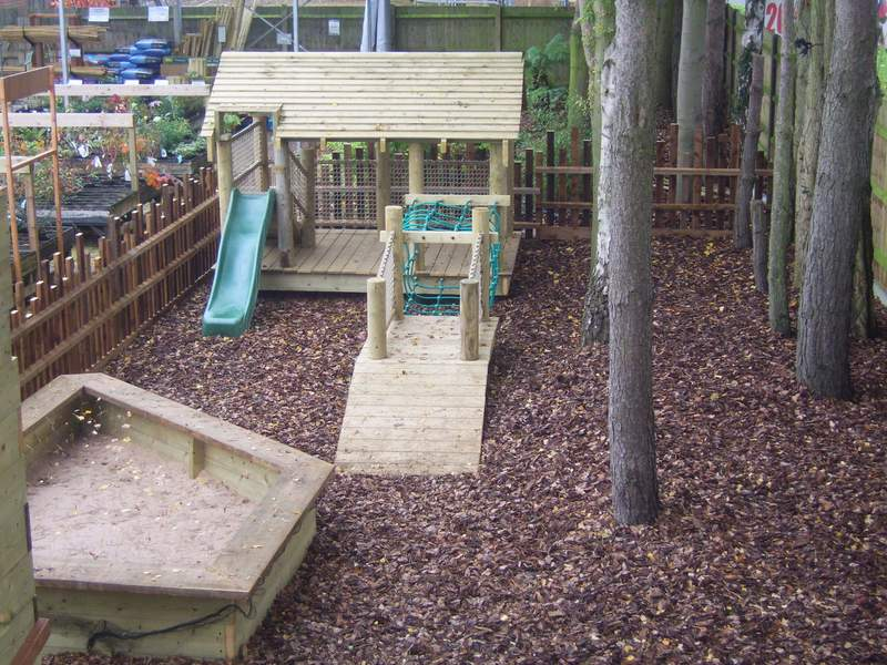 Treetops for the little ones with a small rope bridge, slide, tree house and sand pit